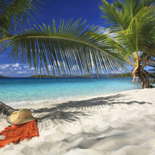 hat and sarong under a palm tree on a gorgeous tropical beach in the caribbean